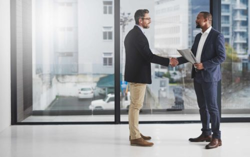 Shot of two businessmen shaking hands at work