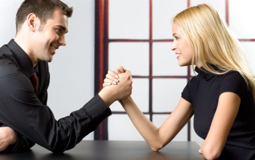 1351376 - young happy couple or business people fighting in arm-wrestling