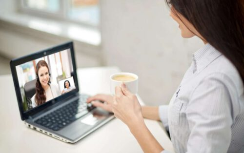 business, technology and communication concept - close up of businesswoman with laptop computer having video call with customer service operator and drinking coffee at office